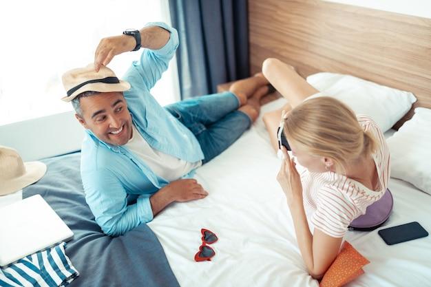 Posando para a câmera. casal casado alegre se divertindo e tirando fotos deitado em uma cama nas férias juntos.