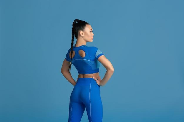 Posando sensual. bela jovem atleta praticando em estúdio, retrato monocromático azul