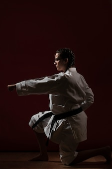 Pose de combate da mulher em uniforme branco de karatê