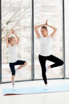 Pose de ioga com a mãe e filha sorridente em casa