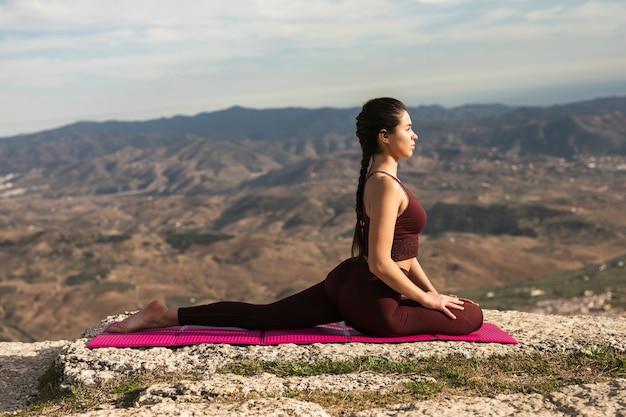 Pose de ioga vista frontal na esteira com fêmea jovem