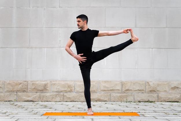Pose de mão estendida para dedão do pé. homem latino atraente fazendo yoga ao ar livre em uma cidade.