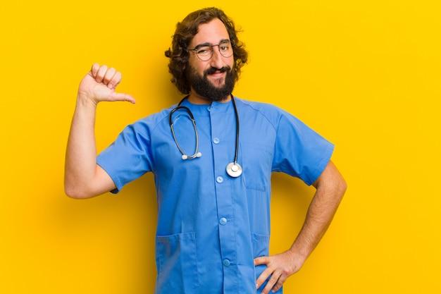 Pose orgulhosa do homem novo da enfermeira contra o fundo amarelo