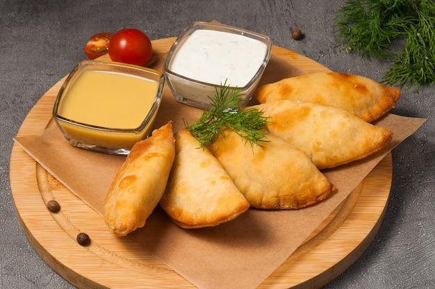 Posekunchiki - tortinhas com carne, com molho de mostarda e creme de leite