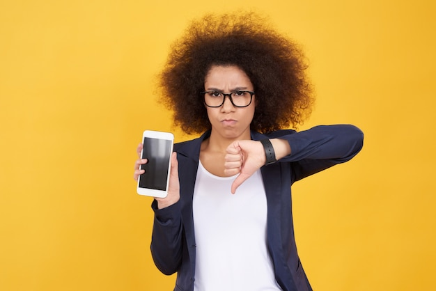 Poses afro-americanos da menina com o telefone isolado.