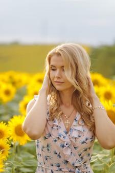 Poses de mulher bonita no campo agrícola com girassol em um dia ensolarado de verão