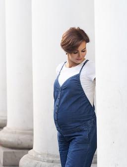 Poses de mulher grávida elegante entre colunas brancas