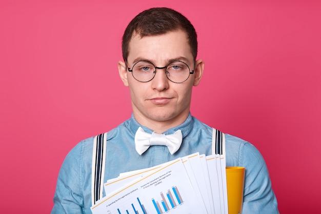 Poses de trabalhador de escritório sem emoção exausto isoladas sobre rosa