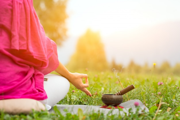 Posição de ioga com sino tibetano