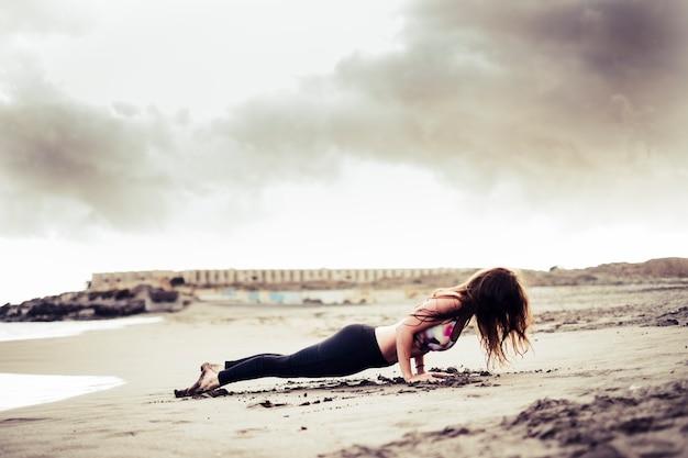Posição de pilates de prancha de doping de jovem garota morena atraente irreconhecível na praia na costa - praticando esportes na natureza ao ar livre - filtro quente e céu nublado