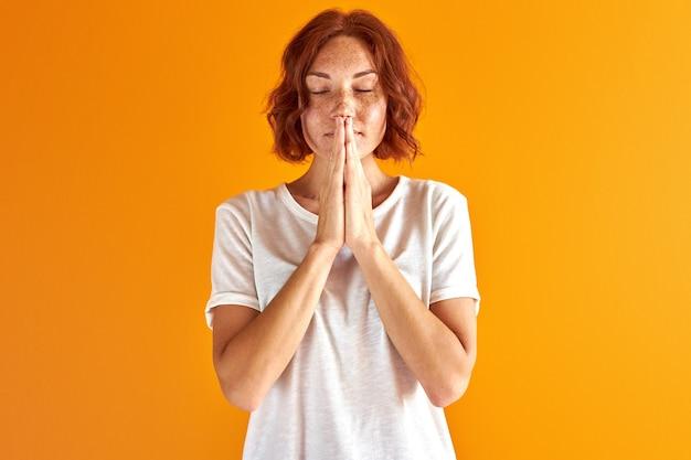 Posição feminina equilibrada com olhos fechados, orando, isolada sobre um espaço laranja