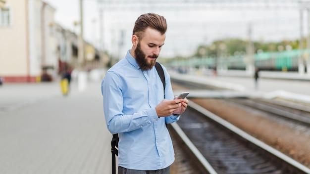 Posição homem, em, estação de comboios, usando, telefone móvel