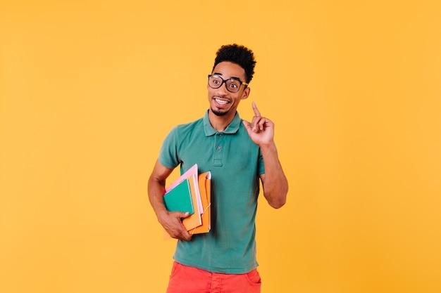 Posição inteligente do estudante internacional. foto de um homem africano em êxtase usa óculos elegantes com livros.