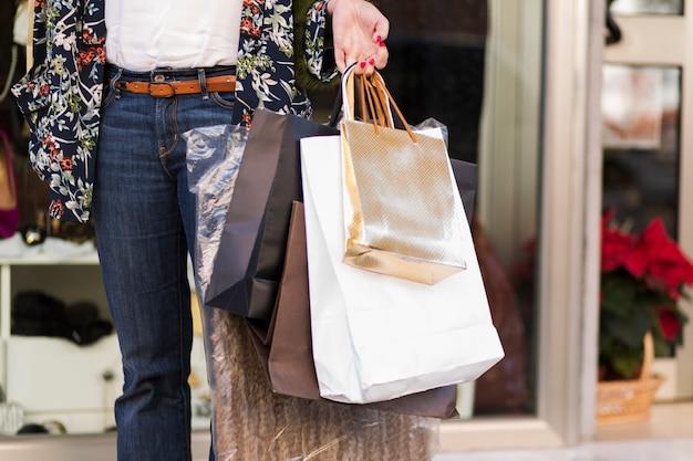 Posição mulher, com, bolsas para compras, ao ar livre