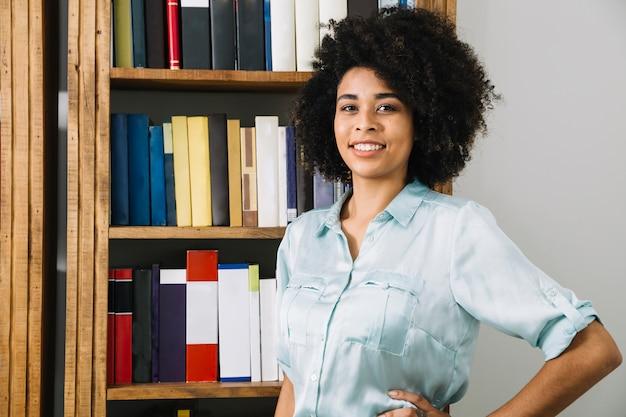 Posição mulher, perto, estante de livros, em, escritório
