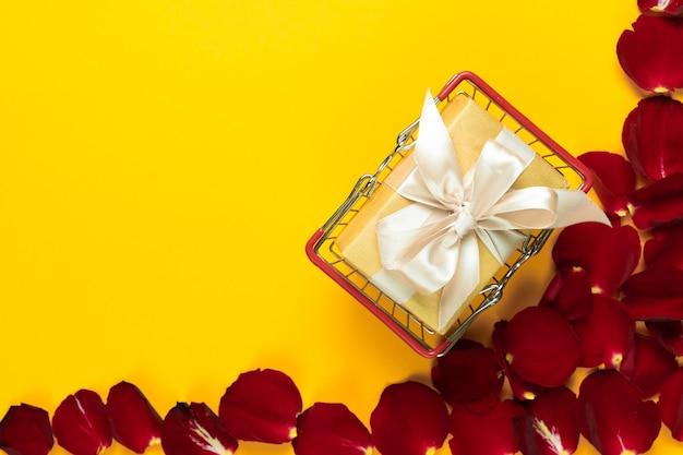 Posição plana, a caixa com laço de cetim encontra-se em uma cesta de compras em um fundo laranja