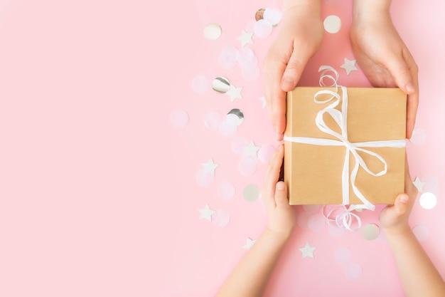 Posição plana com as mãos isoladas dando uma caixa de presente de papel artesanal amarrada com fita, estrela e círculo de confete ou brilhos de papel
