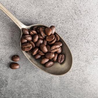 Posição plana da colher de prata com grãos de café