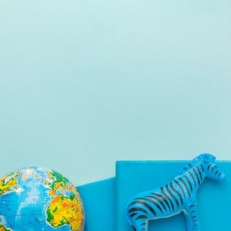 Posição plana da estatueta de zebra com o planeta terra e livros para o dia dos animais