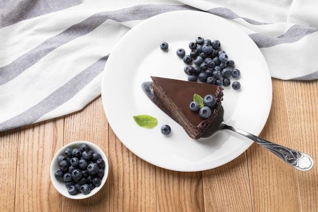 Posição plana da fatia de bolo de chocolate no prato com espátula