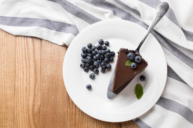 Posição plana da fatia de bolo de chocolate no prato com mirtilos