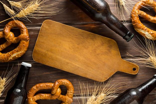 Posição plana da garrafa de cerveja com pretzels e placa de madeira
