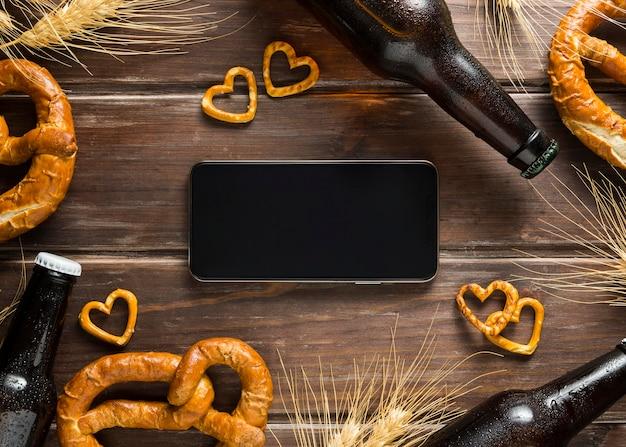 Posição plana da garrafa de cerveja com pretzels e smartphone