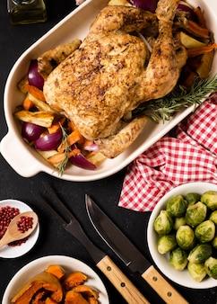 Posição plana da mesa de ação de graças com frango assado e outros ingredientes