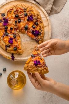 Posição plana da pessoa pegando uma fatia de pizza com caquis e pétalas de flores