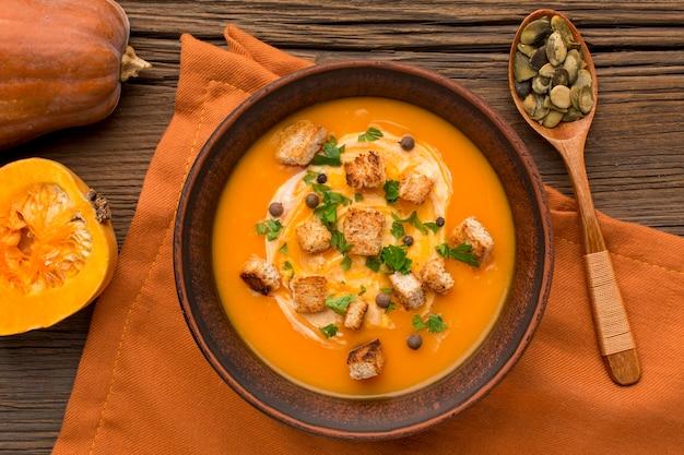 Posição plana da sopa de abóbora com croutons e colher