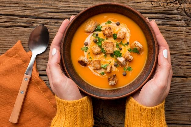 Posição plana da sopa de abóbora em uma tigela segura pelas mãos com uma colher e pão torrado