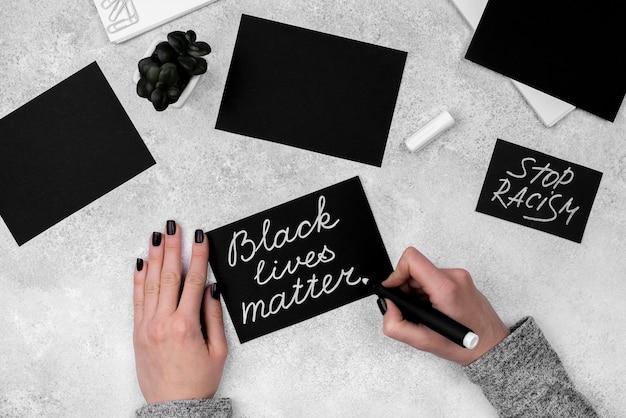 Posição plana das mãos escrevendo matéria de vidas negras no cartão com uma caneta