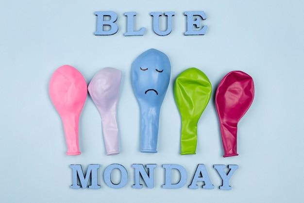 Posição plana de balões coloridos com carranca para segunda-feira azul