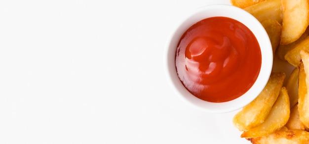 Posição plana de batatas fritas com ketchup e espaço de cópia