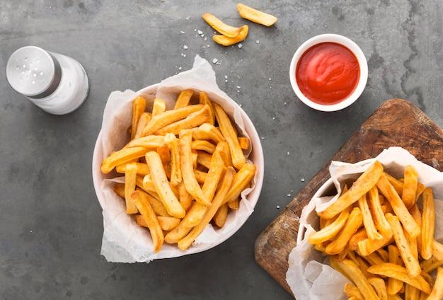 Posição plana de batatas fritas com ketchup e saleiro