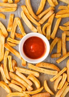 Posição plana de batatas fritas com ketchup