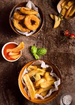Posição plana de batatas fritas com sal e ketchup