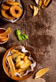 Posição plana de batatas fritas em tigelas com sal e espaço de cópia
