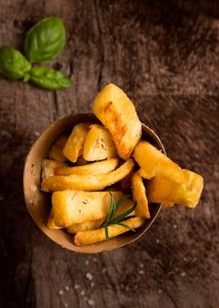 Posição plana de batatas fritas em uma tigela com ervas