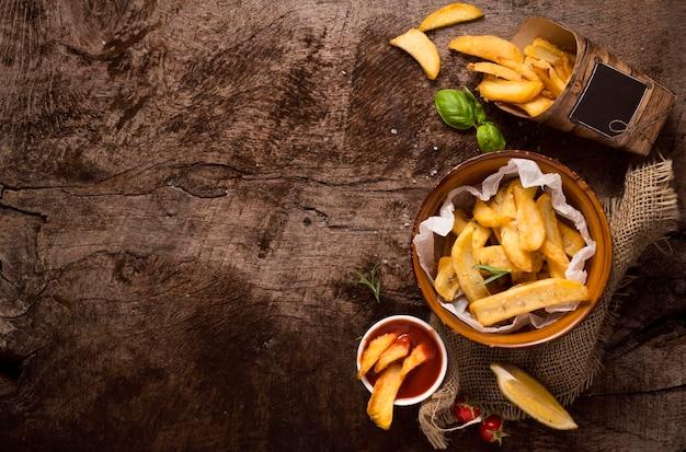 Posição plana de batatas fritas em uma tigela com espaço de cópia