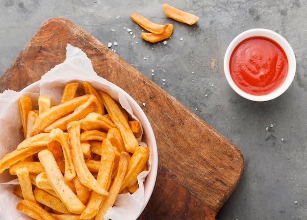 Posição plana de batatas fritas em uma tigela com ketchup