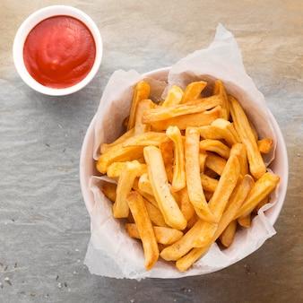 Posição plana de batatas fritas em uma tigela com molho de ketchup