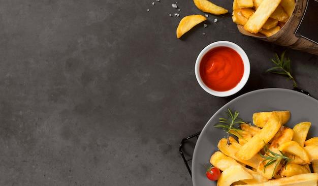 Posição plana de batatas fritas no prato com ketchup e espaço de cópia