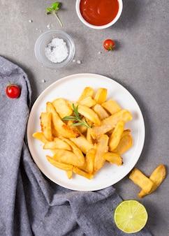 Posição plana de batatas fritas no prato com sal e molho de ketchup