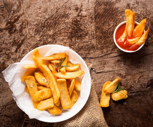 Posição plana de batatas fritas no prato com tigela de ketchup