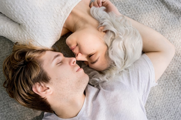 Posição plana de casal romântico relaxando juntos ao ar livre em um cobertor