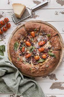 Posição plana de deliciosa pizza fatiada com parmesão