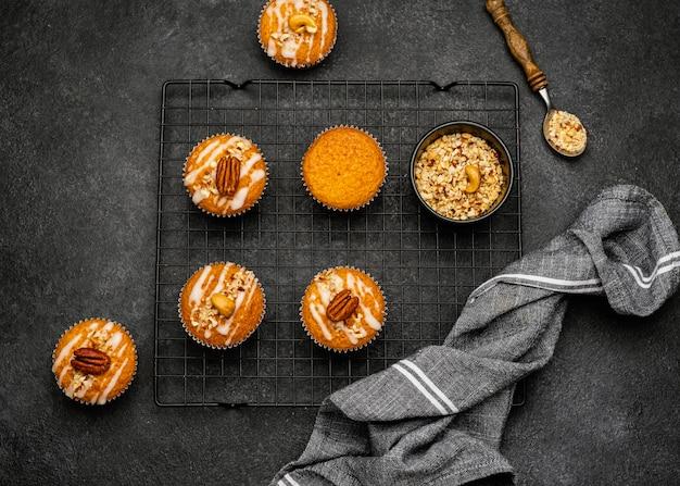 Posição plana de deliciosos muffins com nozes na grade de resfriamento