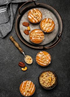 Posição plana de deliciosos muffins com nozes