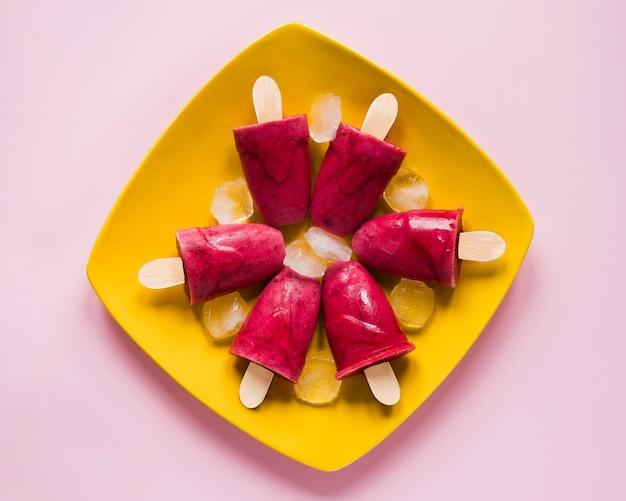 Posição plana de deliciosos picolés no prato com gelo